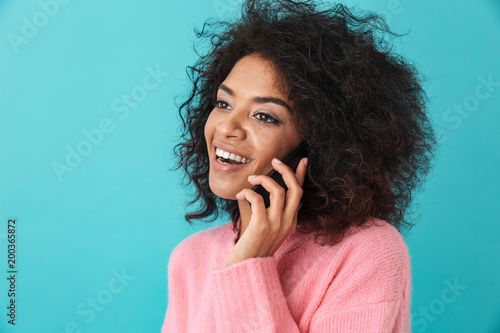 Photo Young happy woman in pink shirt smiling and having mobile conversation, isolated