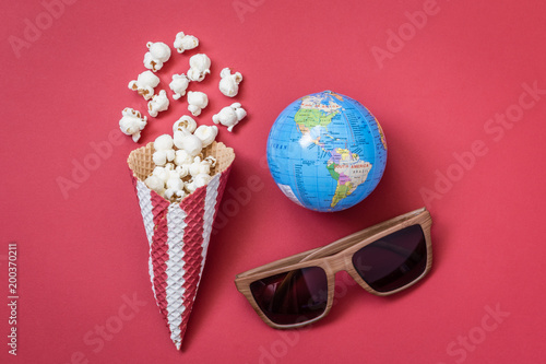 High angle view of cone with popcorn and movie theater eyeglasses with globe model on red background minimalistic concept Wallpaper Mural
