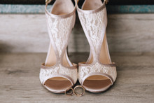 Beautiful Designer Beige Wedding Shoes With Lace, Near Gold Wedding Rings On A Parquet