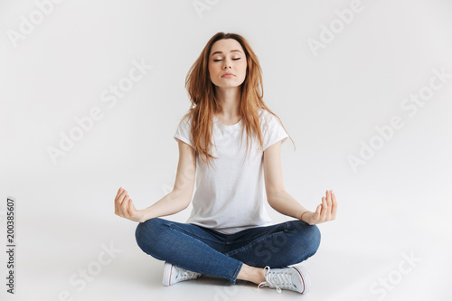 Obraz Calm woman in t-shirt sitting on the floor and meditation - fototapety do salonu