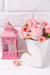 Pink roses flowers in white pot, decorative heart and pinj lantern against white brick wall.