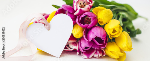 Greeting card - Pink and yellow tulips on a white background