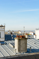 Open view over the rooftops of Montmartre district in Paris with zinc roofing, TV antennas, skylights and a group of chimneys in the foreground under a clear blue sky.