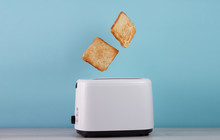 Roasted Toast Bread Popping Up Of Stainless Steel Toaster On A Blue Backgroun.