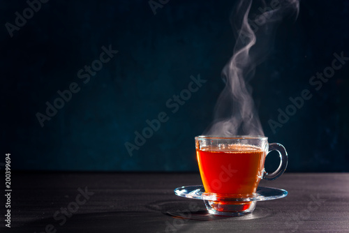 La pose en embrasure The Freshly brewed black tea in a transparent glass Cup,escaping steam,darker background.