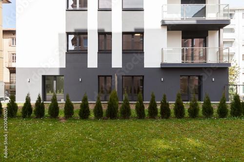 Deurstickers Surrealisme small garden in front of a big build