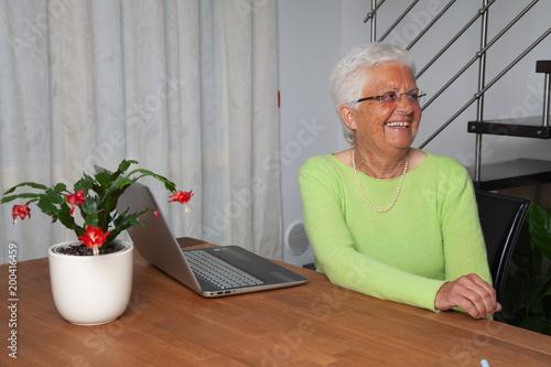 Photo donna anziana sorridente davanti al computer