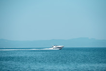High Speed Boat In Sea, Blue Sky And Mountains On Background. Amazing View On White Luxury Yacht Glides On Sea Surface. White Waves After Ship On Beautiful Blue Sea. Tourism And Vacation Concept.