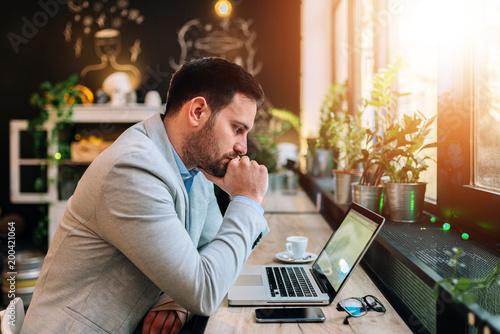 Fotografía  Thoughtful businessman looking at laptop screen.