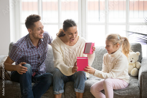 Excited Woman Opening Gift Box With Present From Child Daughter And Husband Sitting On Sofa Together