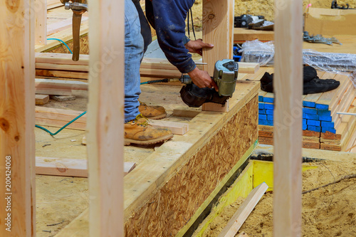 Fotografie, Obraz  Building contractor worker with a air nail gun nailer working on the corner of t