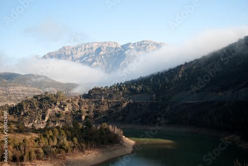 Tuinposter Zwart Embalse con paisaje de montaña y bancos de niebla al fondo.
