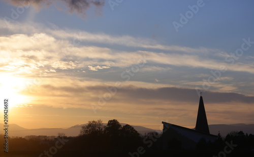Foto op Aluminium Bergen Landscape and church, cross silhouette on cloudy sunset sky