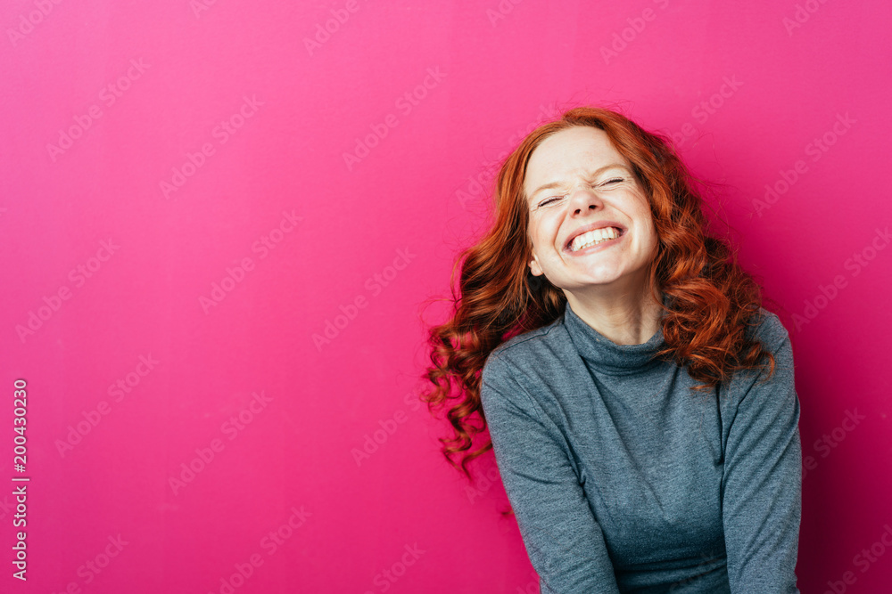 Fototapeta Young laughing woman against pink background