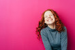 canvas print picture - Young laughing woman against pink background
