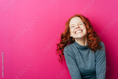 Obraz Young laughing woman against pink background - fototapety do salonu