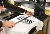 Fototapeta Kuchnia - Young man printing on t-shirt at workshop