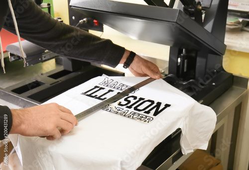 Fototapeta  Young man printing on t-shirt at workshop