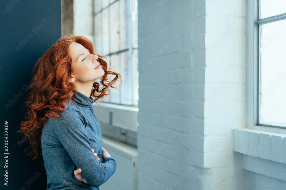Fototapeta Young redhead woman standing daydreaming