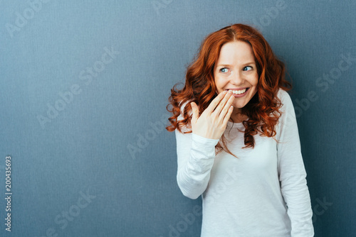 Photo  Cute young woman laughing behind her hand
