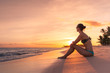 Young woman sitting on beach watching the sunset. Exotic beach holiday getaway.