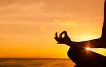 Hand Meditating Against Ocean Sunset.