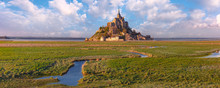 Beautiful Panoramic View Of Famous Mont Saint Michel At Sunset With Reflection In The Canal On The Water Meadows, Normandy, France