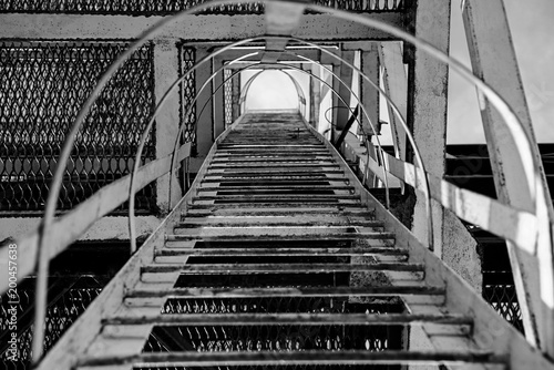 Staande foto Industrial geb. Black and white photo industrial metal staircase up