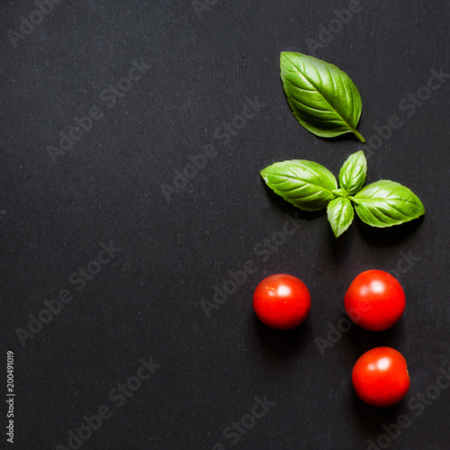Obraz Fresh cherry tomatoes and basil leaf  on black slate stone chalkboard with copyspace. - fototapety do salonu