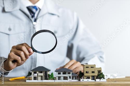 Photo 住宅模型をルーペで覗く作業服の男性