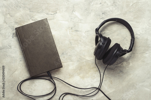 Valokuva Book and headphones connected to it on a white stone background
