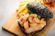 Black burger with fish and shrimps. Fishburger with prawns