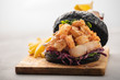 Black burger with fish and shrimps. Fishburger with prawns over light background