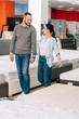 couple holding hands while choosing mattress together in furniture store