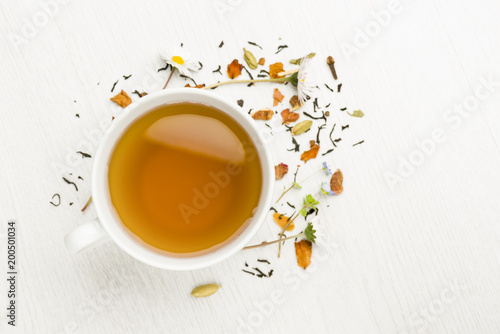 cup of tea on white table with herbs scattered