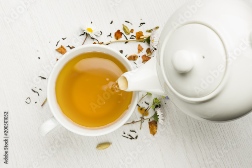 Fényképezés  pouring tea with teapot into cup on white table
