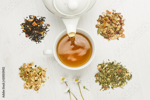 pouring tisane into cup with variety of herbal tea on table