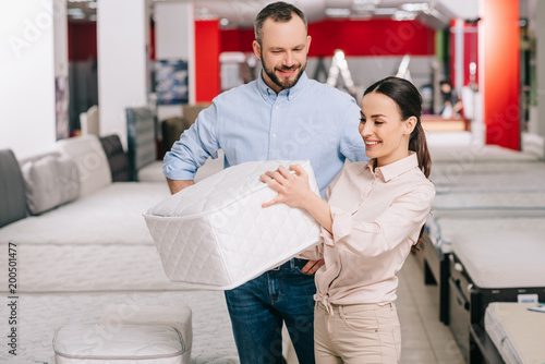 Fotografia  couple choosing folding mattress together in furniture store with arranged mattr