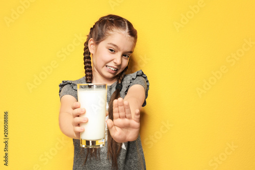 Little girl with dairy allergy holding glass of milk on color background