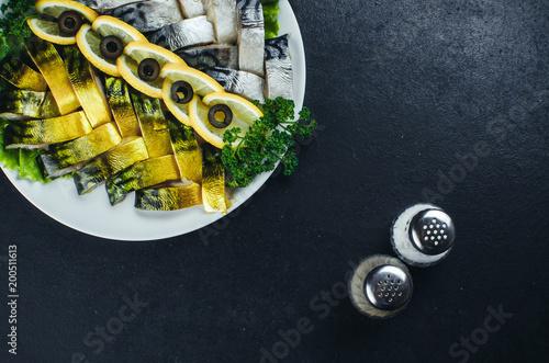 Deurstickers Klaar gerecht On dark fabrics, on the plate is a beautiful fish, herring, and salmon