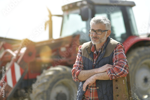 Farmer standing by tractor outside the barn Fototapeta