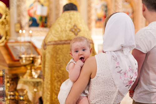 Fotografija Mother holding baby girl in orthodox church during epiphany ceremony