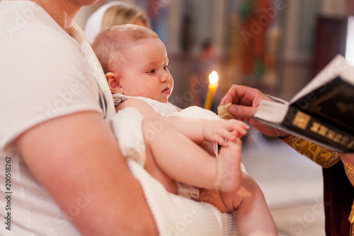 Priest touches the feet of newborn baby during the ceremony of epiphany Poster Mural XXL