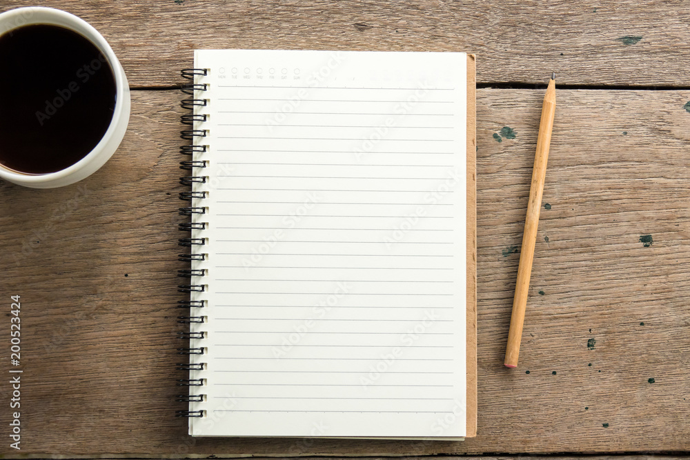 Fototapeta Top view of blank notebook with white coffee and natural light on wooden table.