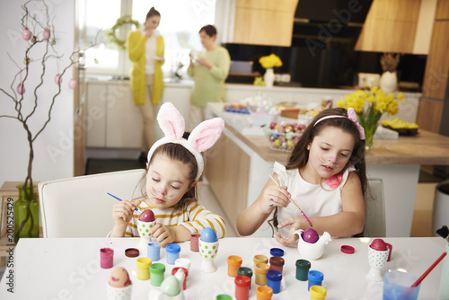 Sisters sitting at table painting Easter eggs