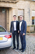The young elegant happy men standing outdoor near a car