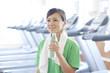 スポーツジムで水を持ち微笑む女性