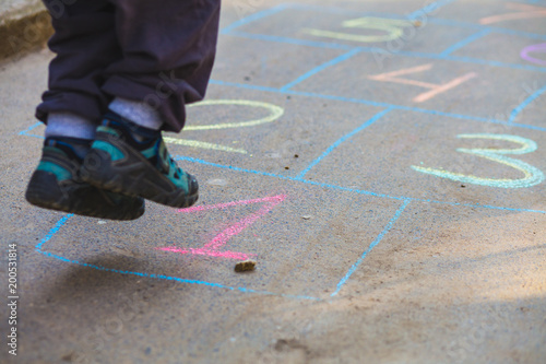 Hopscotch in a schoolyard on an asphalt floor with chalk drawings of numbers and squares as an icon of youth innocence and children playing a fun jumping game at recess or after elementary school Wallpaper Mural