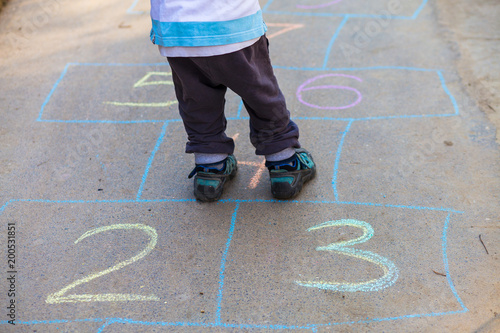 Photo Hopscotch in a schoolyard on an asphalt floor with chalk drawings of numbers and squares as an icon of youth innocence and children playing a fun jumping game at recess or after elementary school