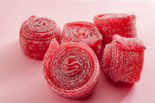 Chewy Sweets And Strawberry And Cherry Flavoured Gummy Candy Concept With Close Up On Sweet And Sour Red Sour Belts Covered In Sugar Isolated On A Pink Background